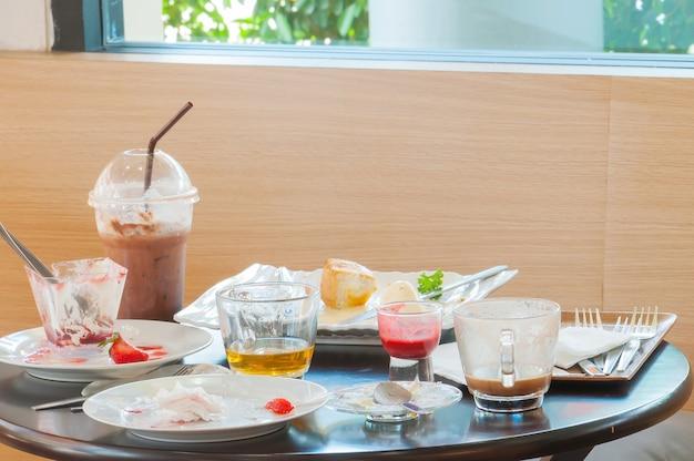 Restos de comida no prato após o café da manhã, comida suja no recipiente sobre a mesa depois de comer