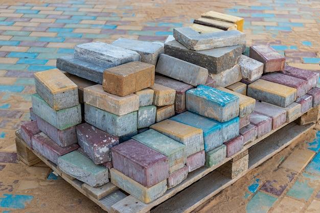 Restos de lajes de pavimentação de concreto multicolorido em um palete após o assentamento da passarela.