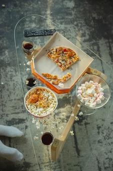 Restos de pizza e pipoca na mesa depois que a família passou um tempo junta, assistindo ao cinema. vista do topo. união, conforto do lar, amor, conceito de relações. alimentos e lanches.