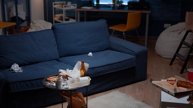 Restos de pizza, garrafas de cerveja vazias e guardanapos na mesa da sala de estar bagunçada