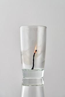 Restos de um fósforo morrendo em um vidro transparente sobre um fundo claro