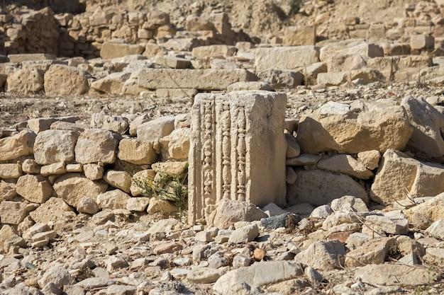 Restos de uma coluna quadrada sobre as ruínas de uma cidade antiga