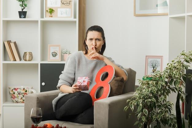 Restrito mostrando gesto de silêncio linda garota no dia da mulher feliz segurando um presente sentado na poltrona na sala de estar