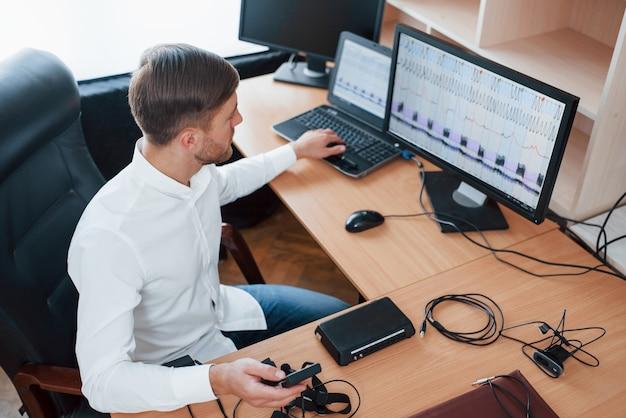 Resultados interessantes. o examinador de polígrafo trabalha no escritório com seu equipamento detector de mentiras