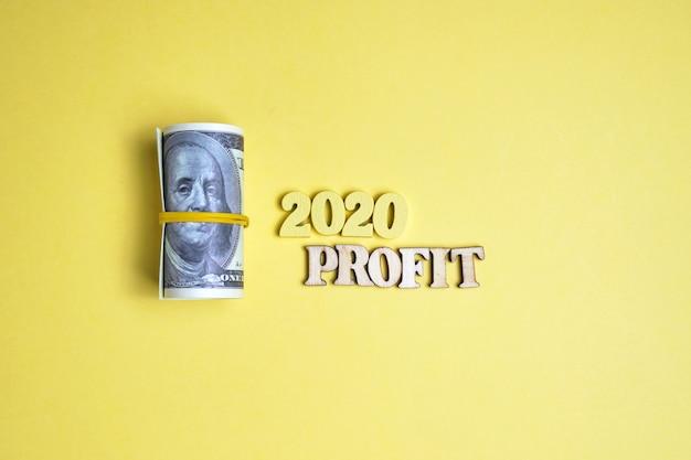 Resumo 2020 de números e letras de madeira com a palavra lucro e um rolo de dólares amarrados com um bandon elástico.