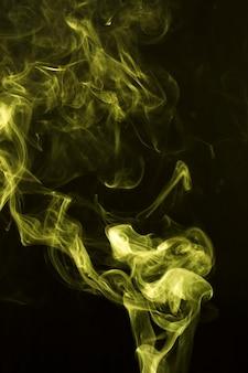 Resumo amarelo soprando fumaça em fundo preto