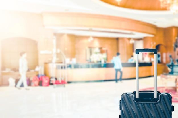 Resumo blur lobby do hotel com recepcionista e saco de bagagem para o fundo