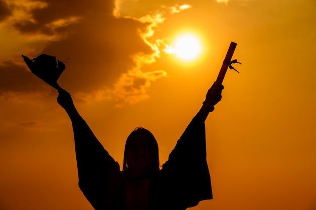 Resumo close-up vista traseira dos graduados da universidade ao pôr do sol silhueta