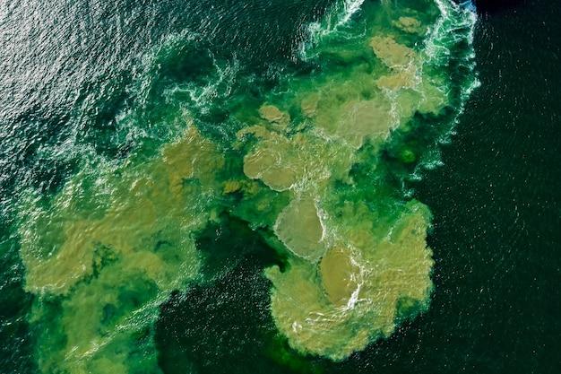 Resumo da água do mar com textura e derramamento de óleo da vista aérea superior do fundo dos barcos a motor