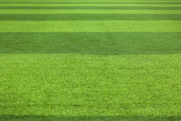 Resumo da superfície da grama do relvado do fundo da grama verde. campo de futebol de grama artificial
