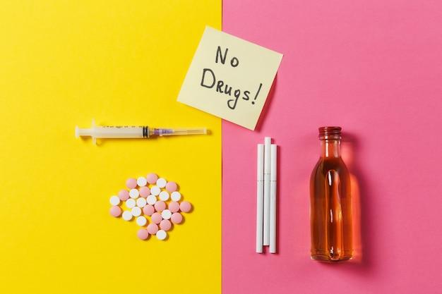 Resumo de comprimidos de comprimidos coloridos de medicação, agulha de seringa vazia, garrafa de álcool, cigarros em fundo rosa rosa amarelo