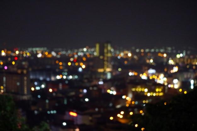 Resumo de cor de desfocar a luz do arco-íris da cidade no céu noturno