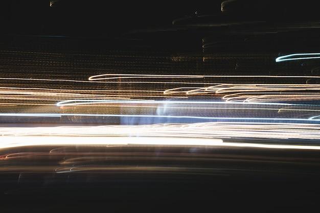 Resumo de feixes de luzes multicoloridas da cidade em movimento, movendo linhas coloridas ou pintura de luz led construindo abstração no fundo de trilhas de luz da cidade ocupada. desigh vertical