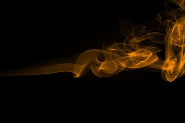 Resumo de fumaça amarela sobre fundo preto, fogo