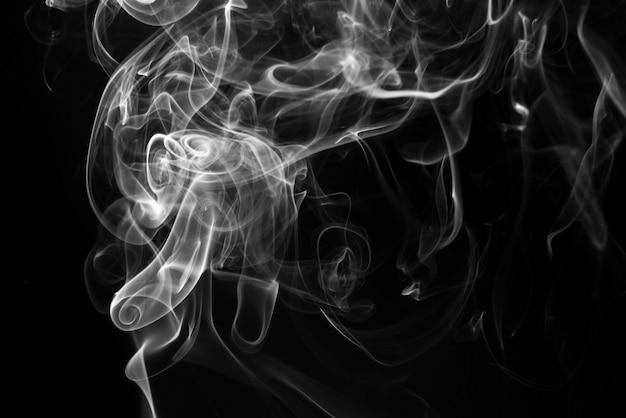 Resumo de fumaça branca sobre fundo preto. fogo . conceito de escuridão