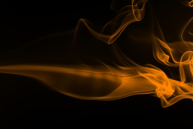 Resumo de fumo amarelo sobre fundo preto, tinta amarela no escuro