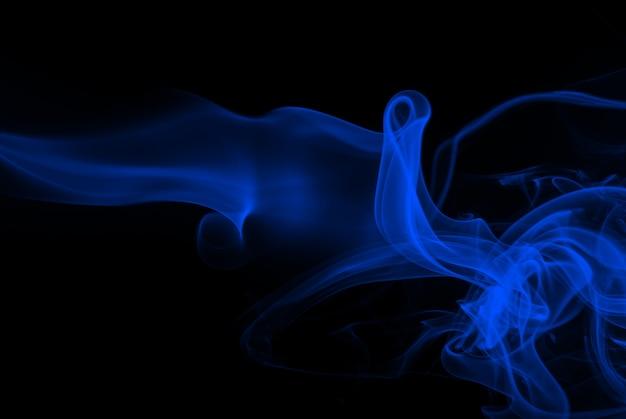 Resumo de fumo azul sobre fundo preto, conceito de escuridão