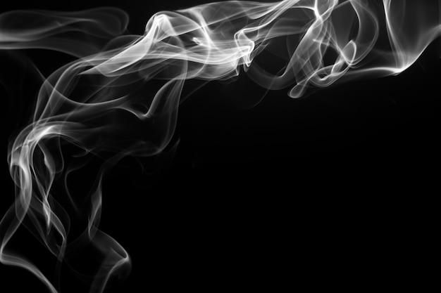 Resumo de fumo branco sobre fundo preto, conceito de escuridão