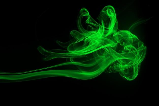 Resumo de fumo verde sobre fundo preto, conceito de escuridão