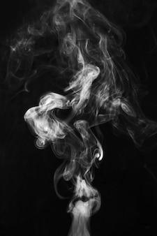 Resumo de redemoinhos esfumaçados branco sobre fundo preto