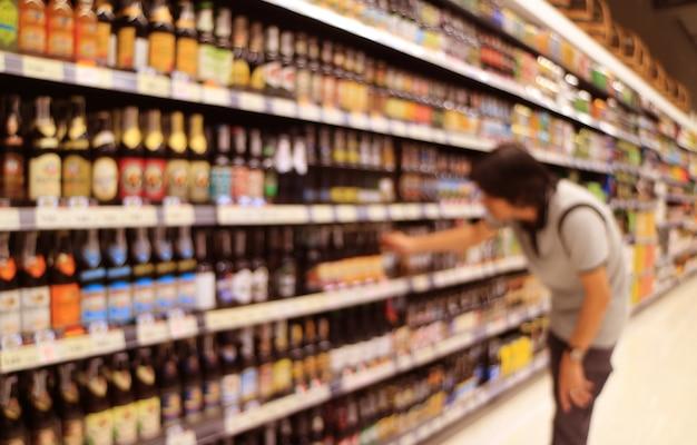 Resumo desfocado de um homem selecionando garrafas de cerveja na prateleira do supermercado