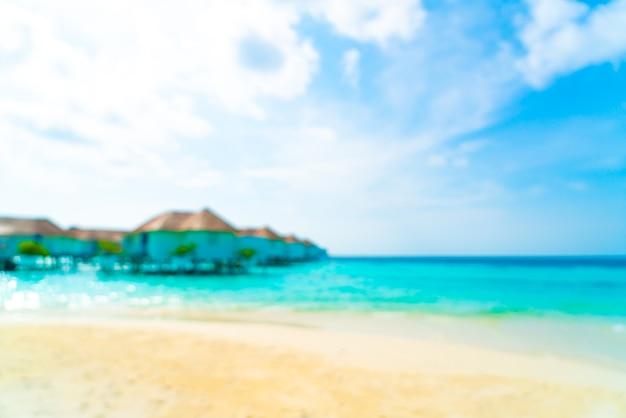Resumo desfocar a praia tropical e o mar nas maldivas como plano de fundo - conceito de férias de férias