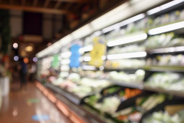 Resumo desfocar frutas e vegetais orgânicos frescos em prateleiras de supermercado em loja de supermercado desfocado bokeh de fundo claro