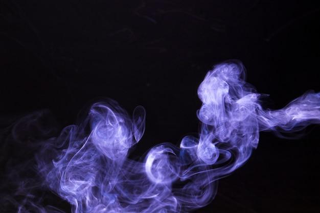 Resumo e textura de fumaça mágica roxa em fundo preto