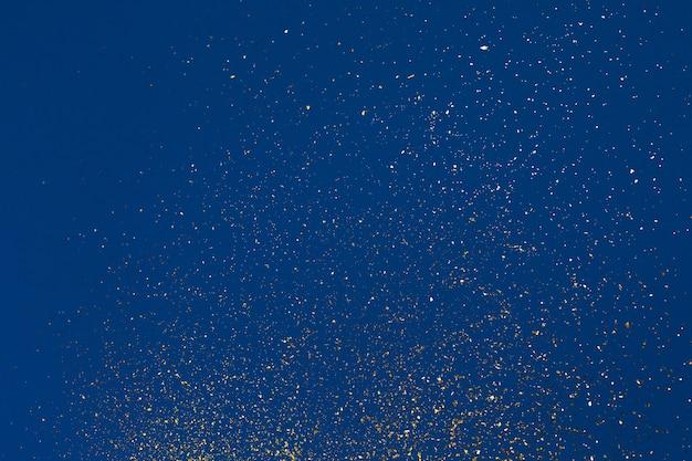 Resumo granulado dourado sobre fundo azul. azul clássico. fundo festivo