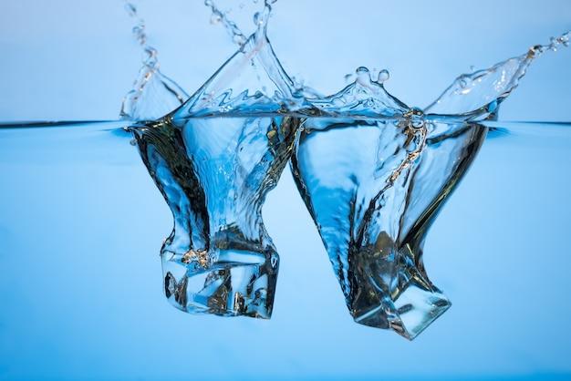 Resumo, minimalista respingo de água com cubos de gelo. bolhas na parede azul.