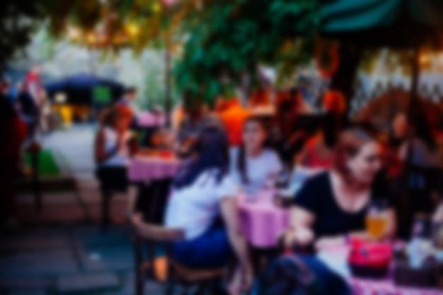 Resumo restaurante ao ar livre turva cheio de convidados à noite