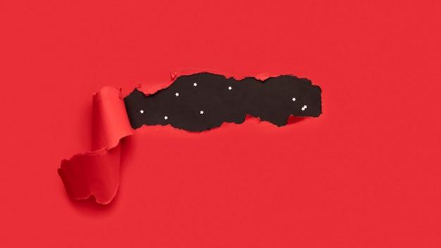 Retângulo de papel rasgado vermelho com fundo preto e estrelinhas douradas