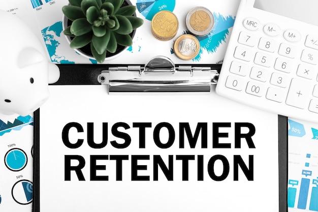 Retenção de clientes de texto na área de transferência. porquinho, moeda, calculadora, gráficos. conceito de negócios. postura plana.