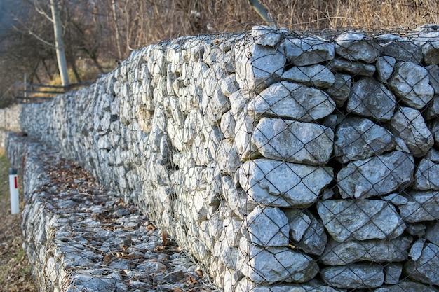 Retendo o muro de pedra ao lado da estrada. faça uma malha de parede gabion.