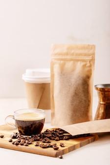 Retire o copo de papel, os grãos de café, a xícara de café expresso, a cezve de cobre e os pacotes de café com espaço em branco para o logotipo sobre a parede branca. copie o espaço
