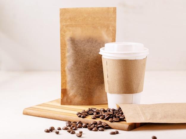 Retire o copo de papel, os grãos de café e os pacotes de café com espaço em branco para o logotipo na parede branca. copie o espaço
