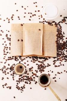 Retire o copo de papel, os grãos de café e os pacotes de café com espaço em branco para o logotipo sobre a superfície branca. copie o espaço. vista do topo