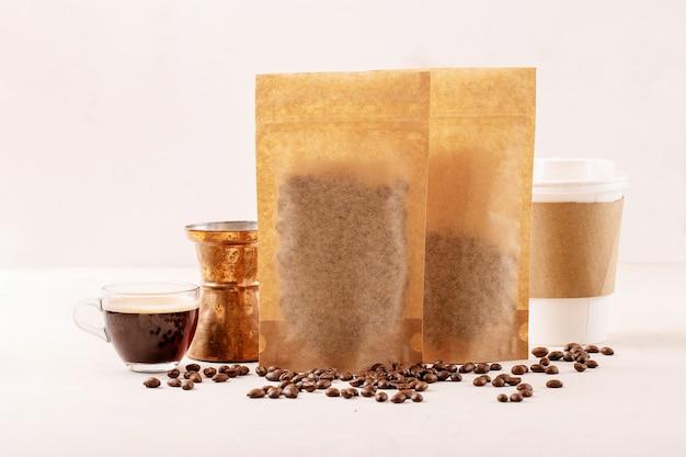 Retire o copo de papel, os grãos de café, o copo de expresso de vidro, o cezve de cobre e os pacotes de café com um espaço em branco para o logotipo sobre a superfície branca copie o espaço