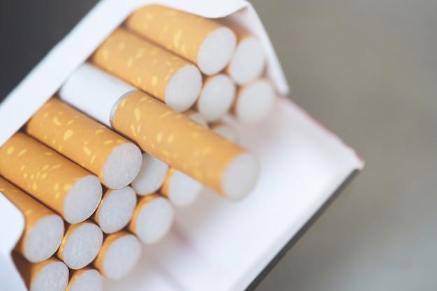 Retire o maço de cigarros, prepare para fumar no fundo branco de madeira