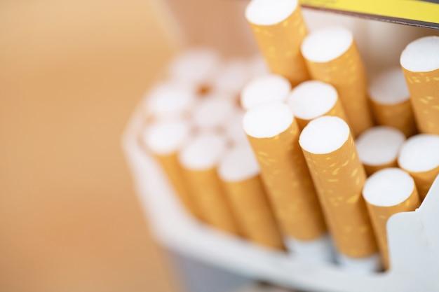 Retire o maço de cigarros, prepare-se para fumar um cigarro. linha de embalagem. filtros fotográficos luz natural. foco suave