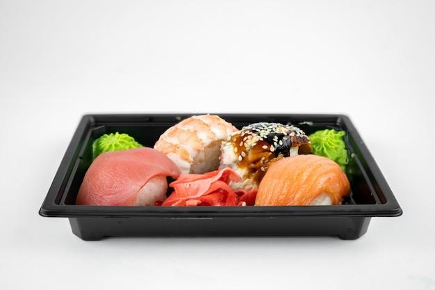 Retire o sushi em um recipiente de plástico, gengibre rosa, wasabi. conceito de entrega de sushi