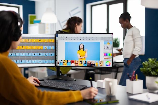 Retocador feminino com fone de ouvido retocando fotos usando caneta stylus desenhando em tablet gráfico, trabalhando em pc com dois monitores