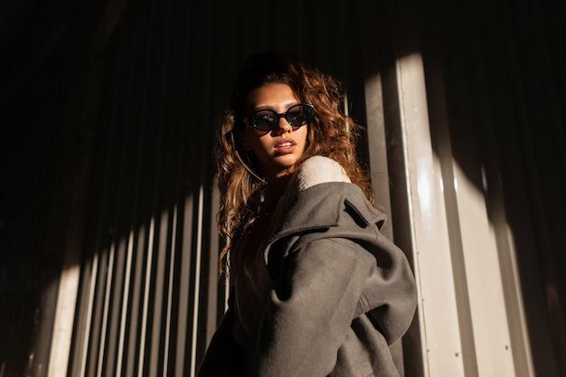 Retrato à luz do sol de uma linda garota na moda com cabelos cacheados em roupas da moda com óculos elegantes e um casaco vintage na rua perto de uma parede de metal na sombra