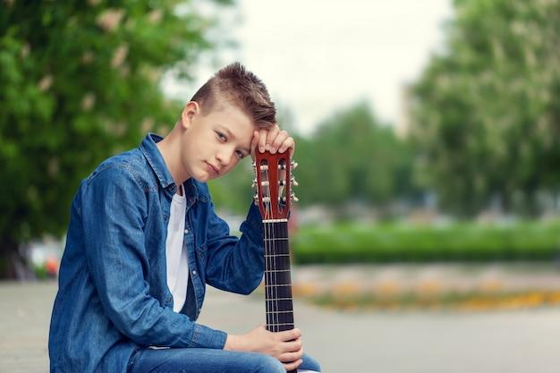 Retrato adolescente menino com guitarra sentado no parque.
