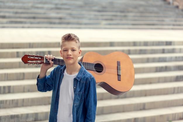 Retrato adolescente menino com violão no parque.
