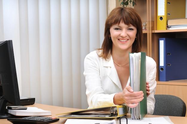 Retrato adulto sorridente linda mulher branca morena branca com uma pasta com documentos na mesa. trabalhador de escritório.