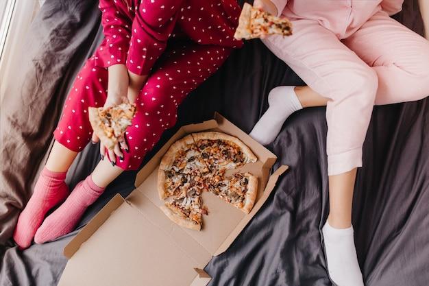 Retrato aéreo de duas garotas de pijama, sentadas na cama com fast food italiano. modelos femininos preguiçosos comendo pizza no lençol escuro.