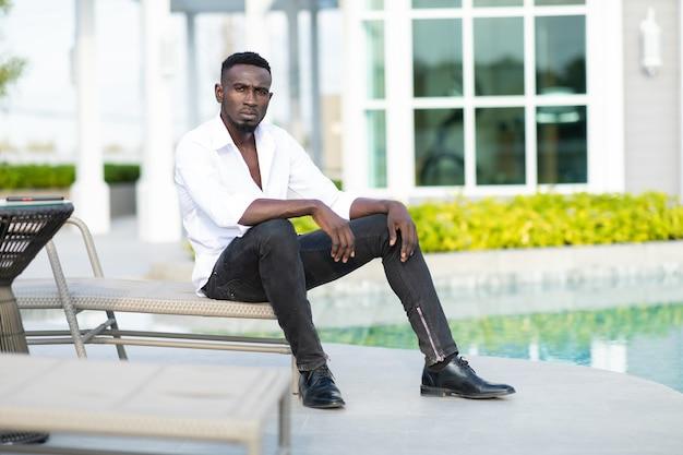 Retrato afro-americano jovem empresário ceo sentado na cama da piscina à beira da piscina na nova casa.