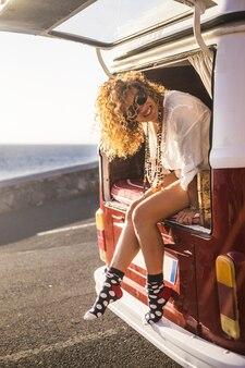Retrato alegre de uma turista linda mulher sentada do lado de fora da porta traseira de sua van, pronta para viajar e aproveitar as férias alternativas de verão