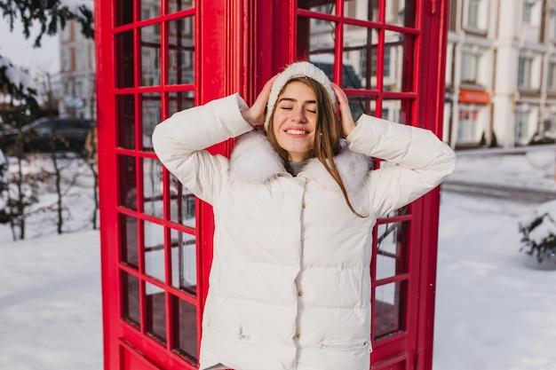 Retrato alegre e incrível jovem em roupas brancas quentes, relaxando no sol na manhã congelada de inverno na cabine telefônica vermelha